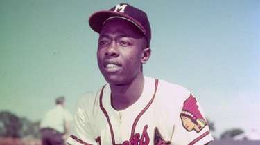 Milwaukee Braves slugger Hank Aaron kneels in the