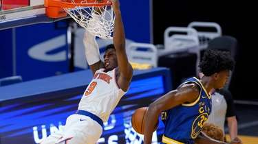 New York Knicks guard RJ Barrett hangs from