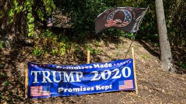 A Trump 2020 sign and a QAnon flag