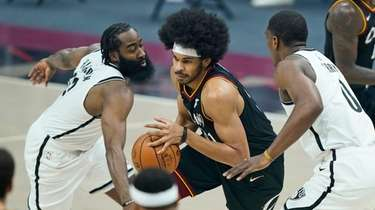 The Cavaliers' Jarrett Allen, center, drives between the