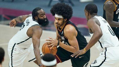 The Cavaliers' Jarrett Allen, center, drives between the