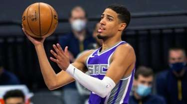 Kings guard Tyrese Haliburton, center, drives to the