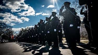 Police officers salute at the funeral for Nassau