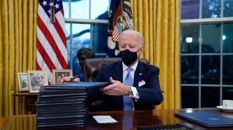 President Joe Biden signs his first executive orders