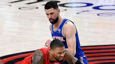 Trail Blazers guard Damian Lillard, center, is fouled