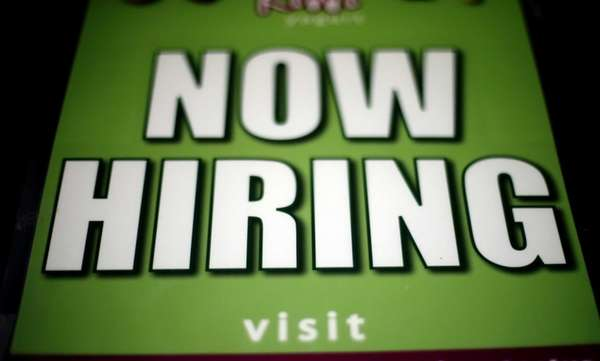 A storefront displays a now hiring sign in