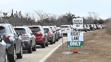 Cars line up at the COVID-19 vaccination site
