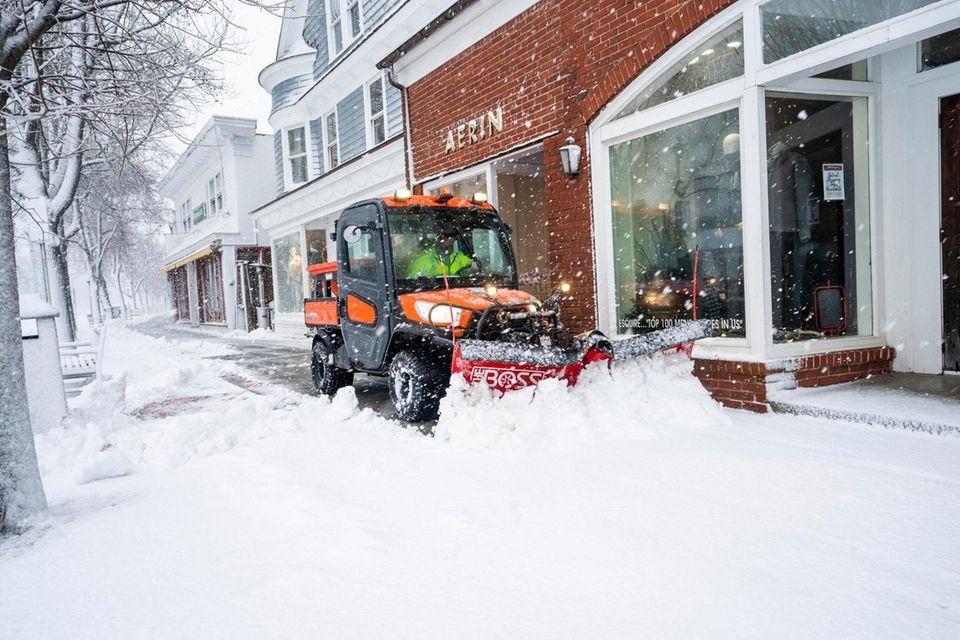 A plow clears the sidewalk on Main Street