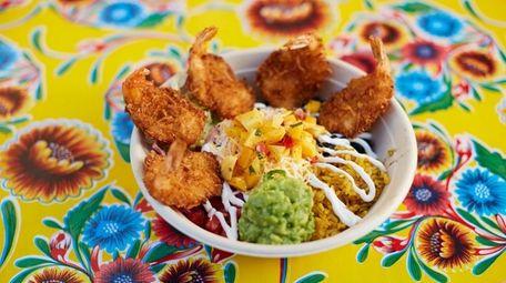 A coconut shrimp burrito bowl with rice, lettuce,
