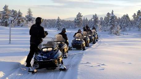 A group of snowmobilers tackle a snowy trail.