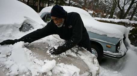 Newton Martin clears the snow in the driveway