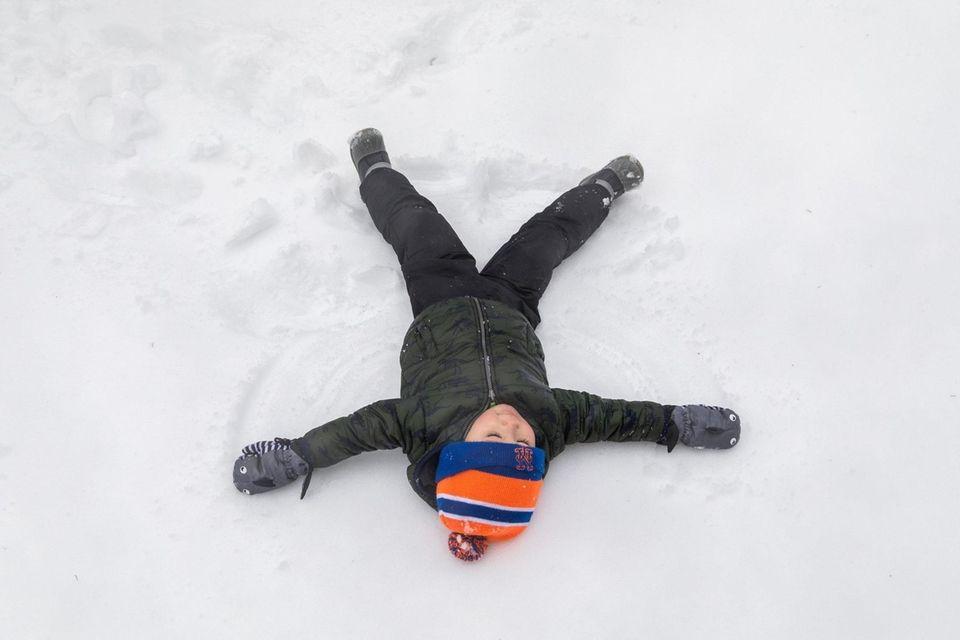 Owen Khottavong, 3, makes a snow angel in