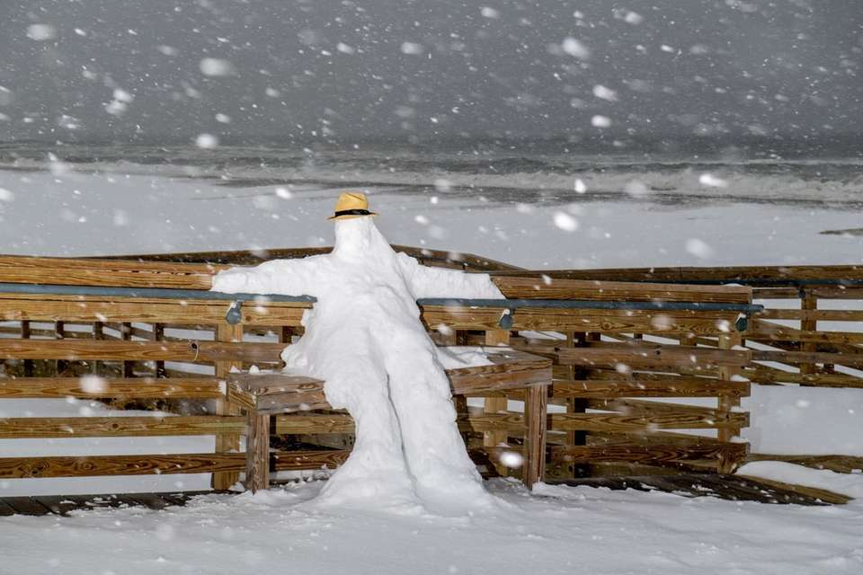 A makeshift snowperson relaxes during a major snowstorm