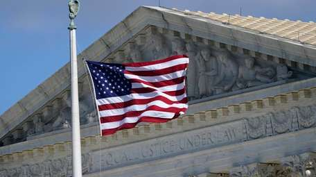 An American flag waves in front of the