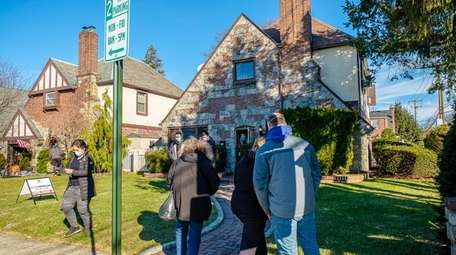 Prospective buyers wait to view a house for