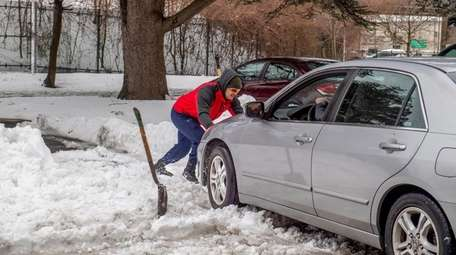 Jorge Espinal digs out a friend's car in