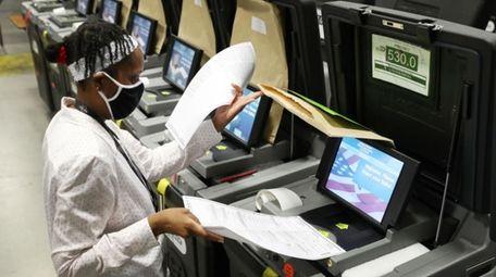 A Miami-Dade election worker feeds ballots into a