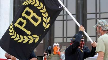 A protester carries a Proud Boys banner in