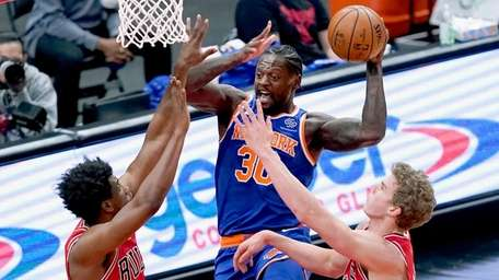 The Knicks' Julius Randle looks to pass between