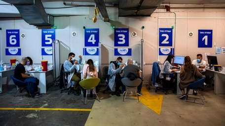 Israelis receive a Pfizer-BioNTech COVID-19 vaccine at a