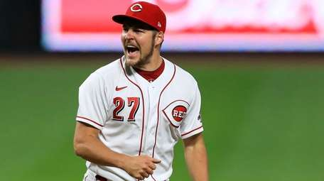 The Reds' Trevor Bauer reacts after recording a