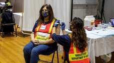 Yessenia Williams gives a COVID vaccine shot to