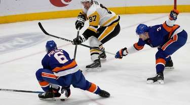 Sidney Crosby of the Penguins plays the puck