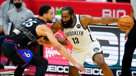 Brooklyn Nets' James Harden (13) tries to drive