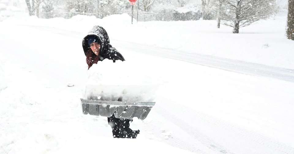 Nicole Rich, shovels snow from the front of