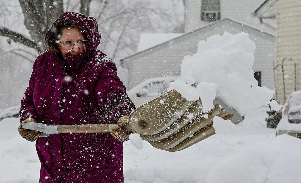 Arlene Holm of Centereach, clears her driveway of
