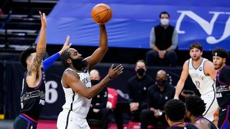 Nets' James Harden, center, goes up for a