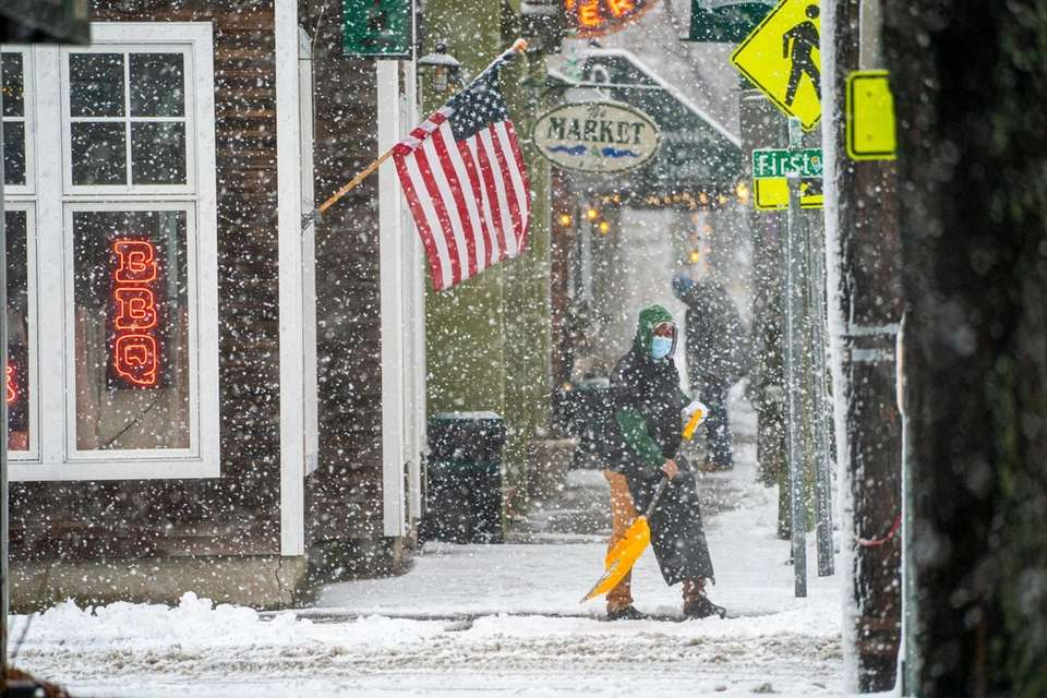 A man shovels snow from a sidewalk on