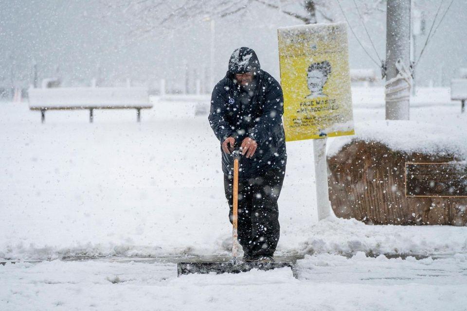 A Greenport Village employee shovels snow on Front