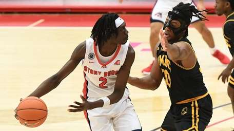 Stony Brook forward Mouhamadou Gueye is defended by