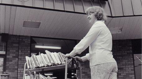 An employee wheels a cartload of books toward