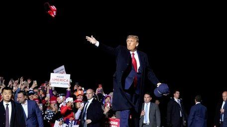 Then-President Donald Trump tosses MAGA hats at a