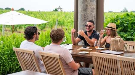 Guests sip wine on the terrace at Wölffer