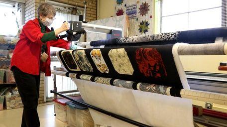 Associate Anne Hennig uses a machine to sew