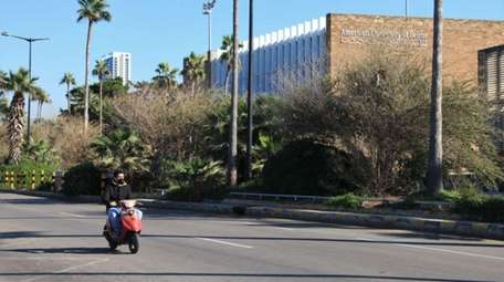 A man riding a motorbike passes by American