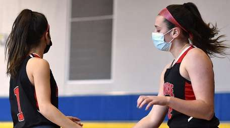 Emily Tierney of Plainedge, right, gets congratulated by