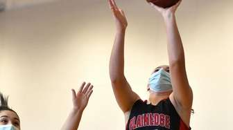 Emily Tierney #12 of Plainedge, right, scores from