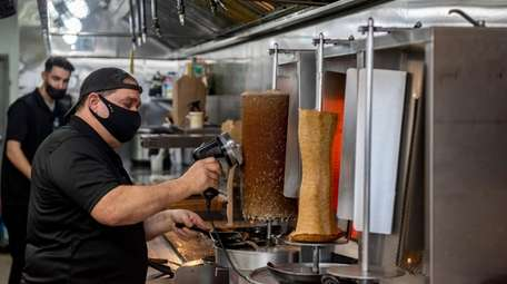 Chef and co-owner Steve Leunes shaves meat during