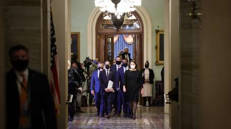 House impeachment managers depart the Senate Chamber at