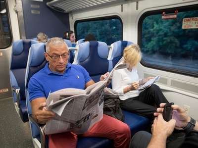 Commuter Chris Smart of Huntington reads the paper