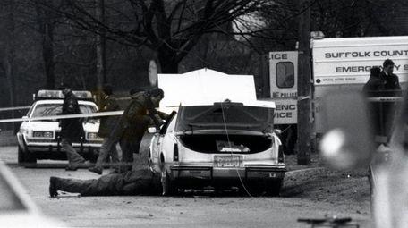 Investigators look under a car on Maple Avenue