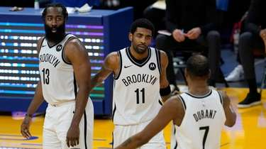 Nets guard Kyrie Irving, middle, gathers with guard