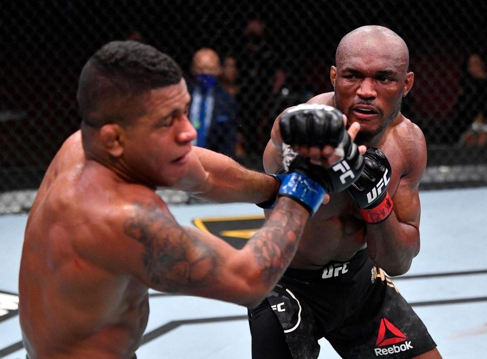 Kamaru Usman of Nigeria punches Gilbert Burns of