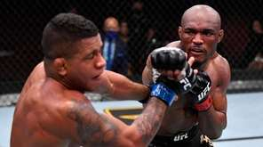 Kamaru Usman of Nigeria punches Gilbert Burns of