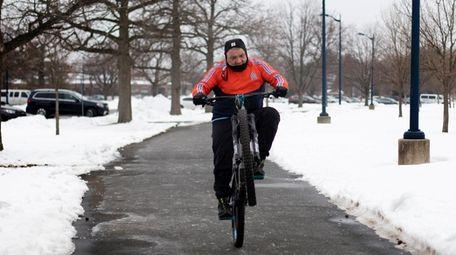 Alex Falconi, of Freeport, rides his bike on