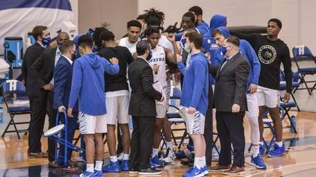 The Hofstra men's basketball team huddles during a